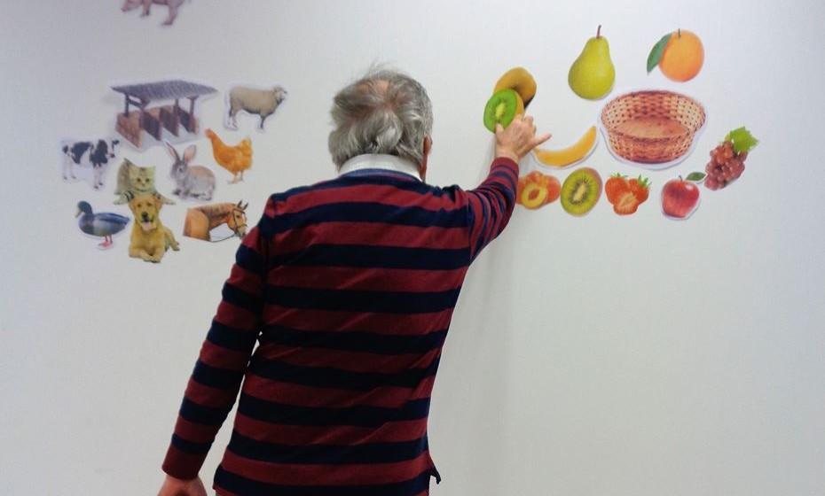 Treino de equilíbrio na posição de pé, com uma atividade cognitiva de categorização semântica (exemplo da imagem: colocar as frutas no cesto e os animais junto do estábulo).