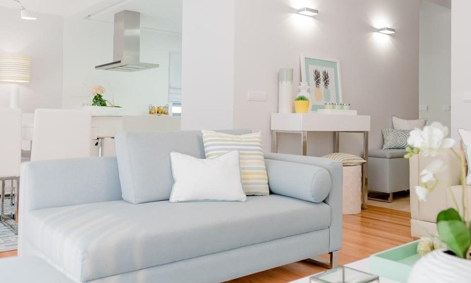 A conjugação dos têxteis de cores claras com os móveis lacados a branco conferem frescura e leveza à sala.