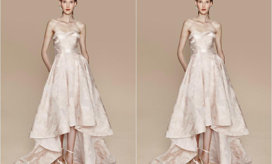 O corte deste vestido surpreende na parte da frente, deixando descobertas subtilmente as pernas. Um vestido de Marchesa.