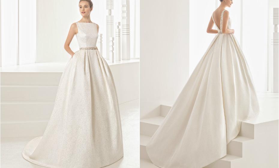 Este vestido de corte clássico da Rosa Clará apresenta um decote em barco e umas costas bem decotadas, saia com pregas e bolsos.