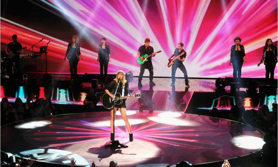 Para esta performance, a cantora Taylor Swift escolheu um macacão preto com vários detalhes em renda e algum brilho. Para completar, utilizou uns botins pretos. Pode ser uma ideia para uma saída mais arrojada, certo?