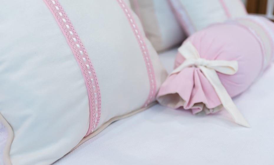 Almofadas com renda e laços personalizam o tema romântico do quarto.