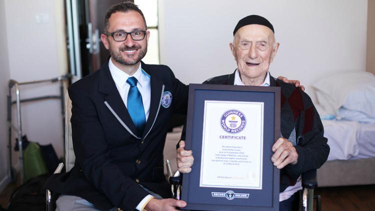Foto: Marco Frigatti, responsável pelo Livro dos Recordes do Guiness, ao lado de Yisrael Kristal, quando tinha 112 anos  e recebeu o certificado de homem mais velho do mundo.