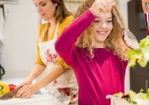 Mother and daughter working in kitchen at home