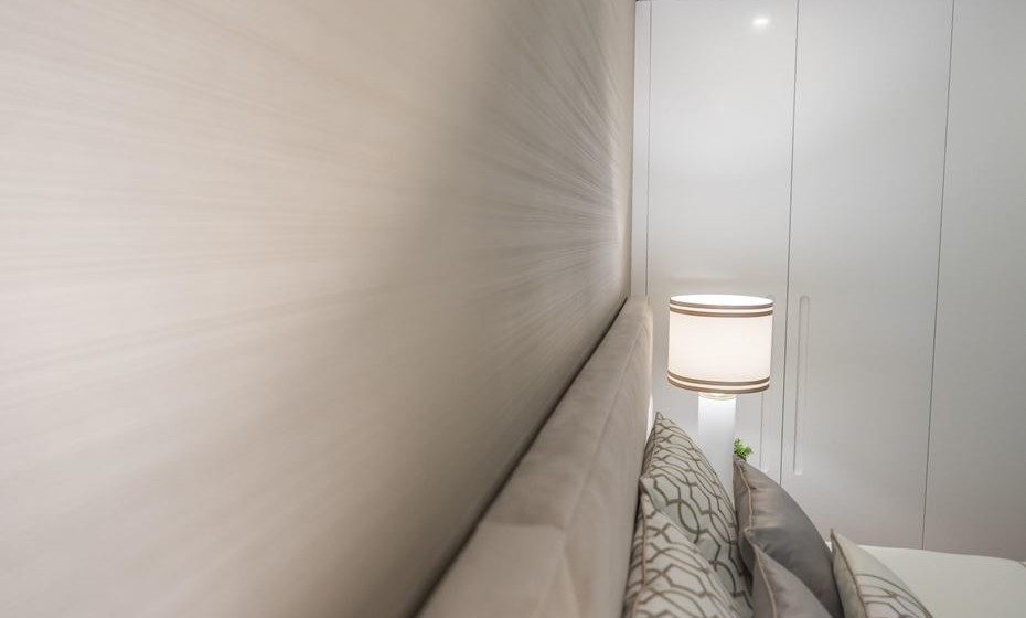 Aplicar papel de parede na cabeceira da cama vai adicionar conforto visual extra. Escolha um papel de parede texturado num tom neutro. Será o ideal.