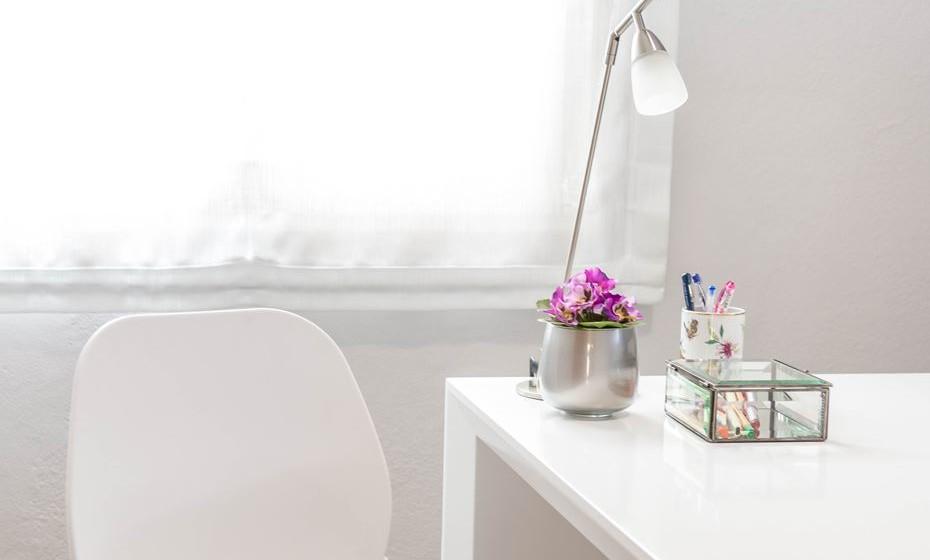 Um local com luz natural é obrigatório. Complemente com um candeeiro de secretária, para tarefas que exijam mais luz. Isso ajuda a evitar cansaço visual e dores de cabeça. Enquadre o candeeiro com um porta lápis, uma moldura ou uma pequena flor.