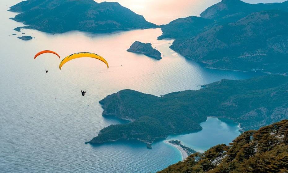 """Sobrevoar a Lagoa Azul em Oludeniz, na Turquia, vai mostrar-lhe vistas deslumbrantes. Oludeniz tem uma das praias mais bonitas de Turquia, com margens de seixos e uma """"lagoa azul"""" em tons de água marinha. A praia também é um dos melhores lugares do mundo para parapente, graças ao clima estável e às belas vistas panorâmicas."""