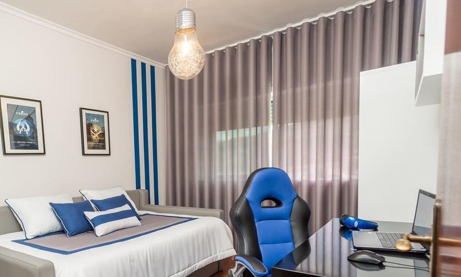 Opção para um quarto jovem e masculino, com uma cortina escura para diminuir a entrada de luz e facilitar a leitura do ecrã do computador.