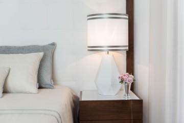 A iluminação é muito importante num quarto, escolha abatjours de tela clara, para ajudar a difundir a luz. O suporte, neste exemplo é em cerâmica, mas podia ser em madeira. Mas como as mesinhas de cabeceira são em madeira, optamos por um material diferente. Para o toque primaveril, um pequeno vaso metálico com um raminho de flores (fica sempre bem).