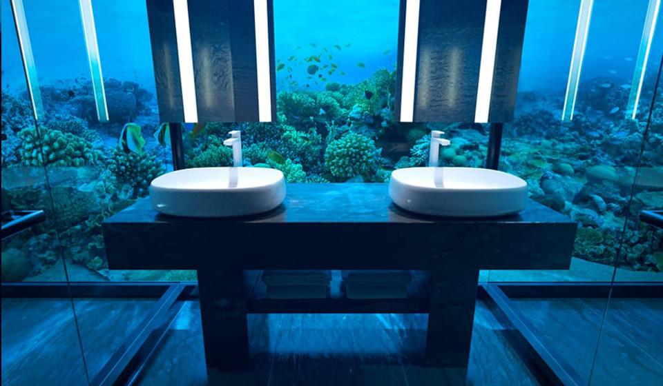 – Casa de banho inferior com lavatórios duplos e um ambiente acolhedor sob os tons azuis e verdes do mar.