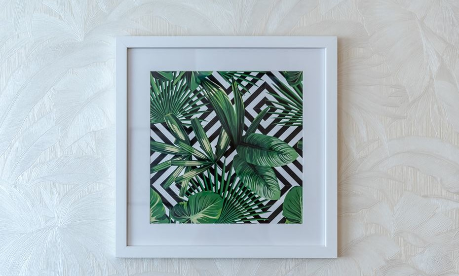 Coloque objetos com motivos tropicais, como quadros com desenho de folhas. Adicione elementos até ao ponto do quarto conter a intensidade tropical que deseja.