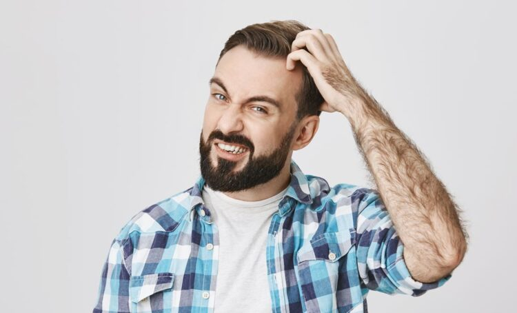 homem coça o cabelo com caspa