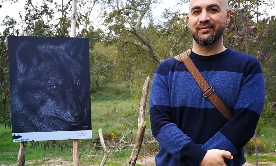 O ilustrador João Simões ao lado do quadro que mais gozo lhe deu fazer