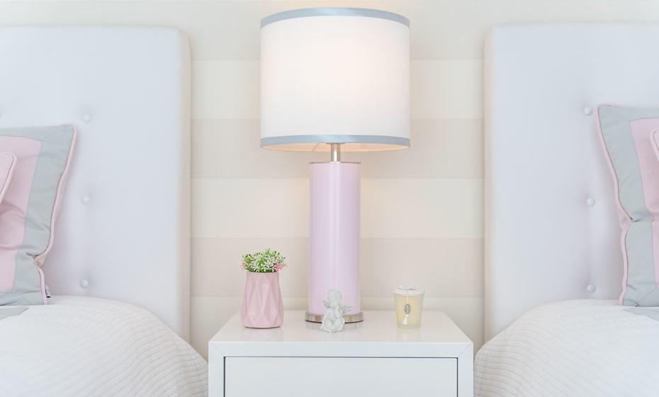 Para criar alguma dinâmica na decoração, escolhemos um candeeiro com os tons da decoração do quarto. O pé cor de rosa e o abatjour com a linhas em cinzento são o detalhe perfeito para completar o look deste quarto.