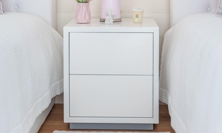 Optamos por colocar apenas uma mesinha de cabeceira, branca e de design sóbrio para ajudar na interligação das camas. Recomendamos que opte por uma carpete de pelo baixo, de tons claros e de fácil manutenção.