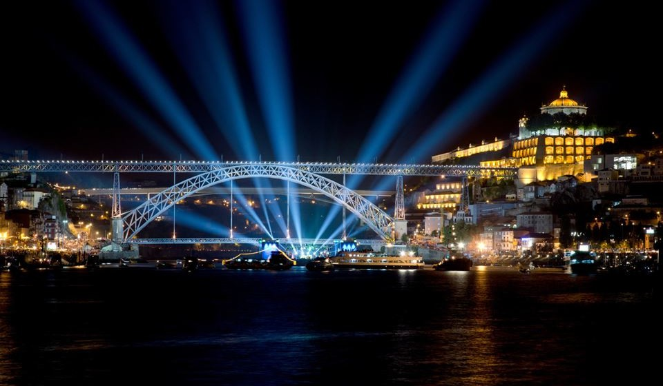 Dom Luis I bridge at night, during a music concert and blue light rays on the dark sky and boats on the water.