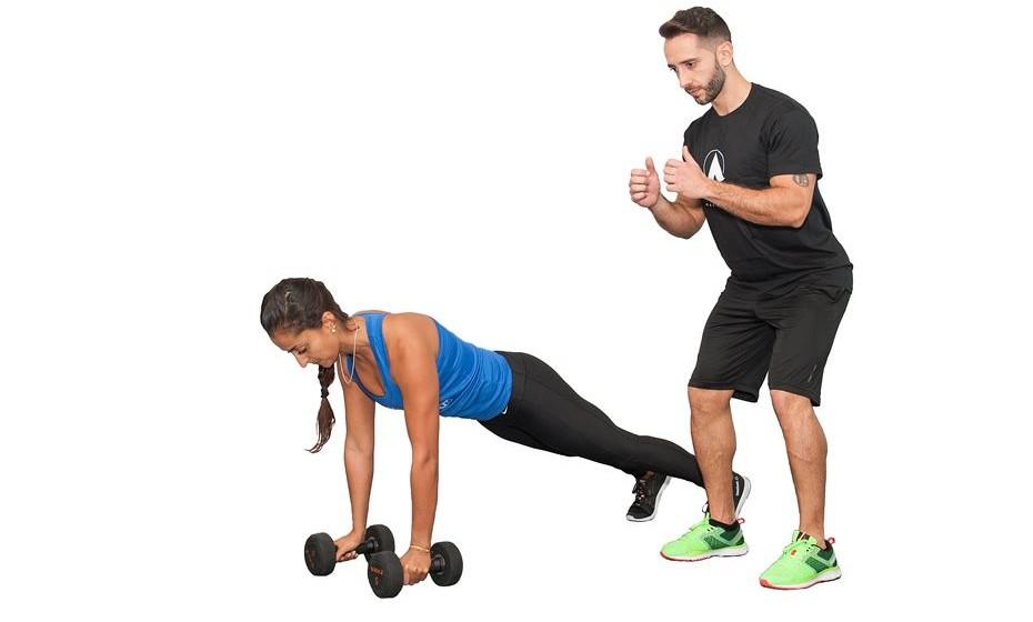 3) 20 remadas com extensão de tríceps em prancha + salto lateral - Em prancha, segure os halteres em baixo dos ombros, puxe o cotovelo à cintura e em seguida estenda o cotovelo. Retome e faça o mesmo para o outro lado. Realize o exercício de maneira alternada. Enquanto um completa as remadas, o companheiro fica a saltar de lado, passando para o outro lado das pernas de maneira contínua.