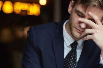 homem cansado com mão na cara