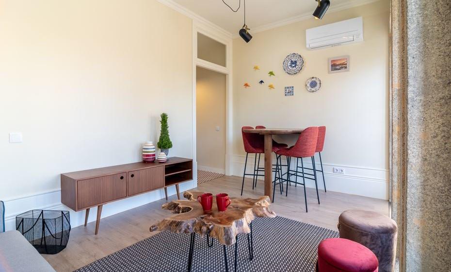 Na sala era necessário a integração de um sofá cama e uma mesa para quatro pessoas.  A escolha de materiais nobres como a nogueira maciça da mesa de jantar, conjugados com artigos típicos portugueses e a contemporaneidade do candeeiro de tecto, completam o estilo eclético deste apartamento.