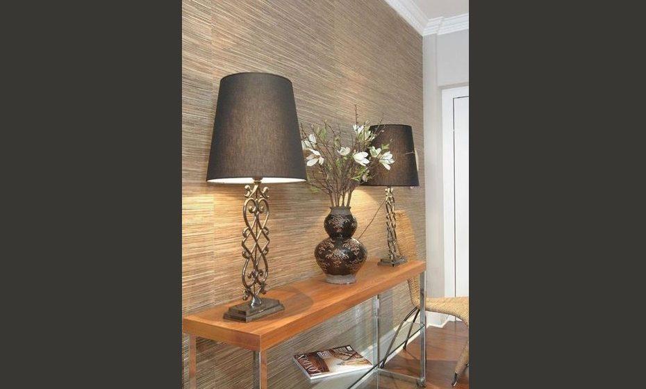 Papel de parede com textura e fibras naturais em tons castanho combinado com móveis em vidro e metal conferem elegância e modernismo.