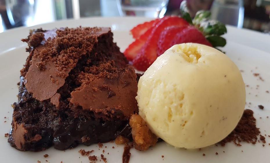 Bolo de chocolate com gelado de baunilha e morangos.