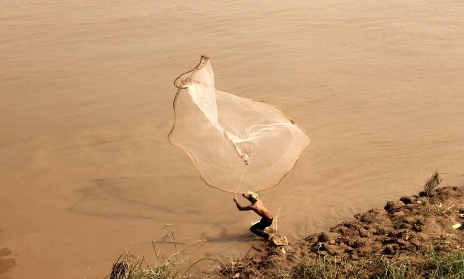 Um homem pesca nas margens do rio Mekong, que atravessa a cidade.