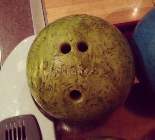 Uma bola de bowling esconde um rosto intrigado.